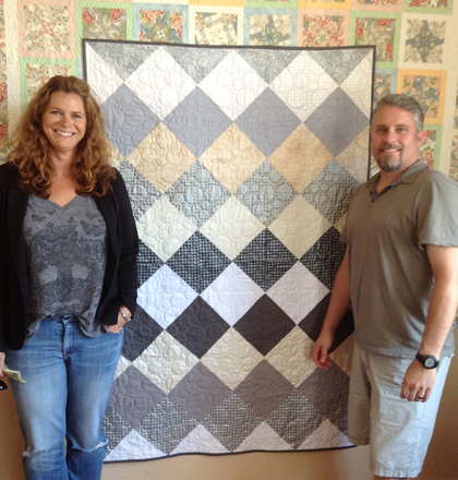 A happy couple holding a quote done by Susan K. Quilting